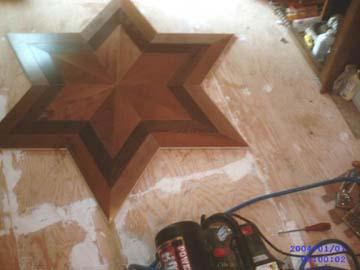 le début de la pose d'un plancher de bois franc avec motif en étoilé de 6 branches.